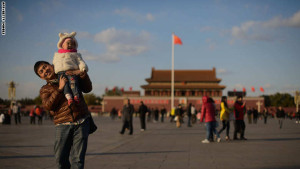 """A man and child walk on Tiananmen Square in Beijing on November 17, 2013. On November 15 China's Communist rulers announced an easing of the country's controversial one-child policy as part of a raft of sweeping pledges including the abolition of its """"re-education"""" labour camps and loosening controls on the economy. AFP PHOTO / Ed Jones (Photo credit should read Ed Jones/AFP/Getty Images)"""